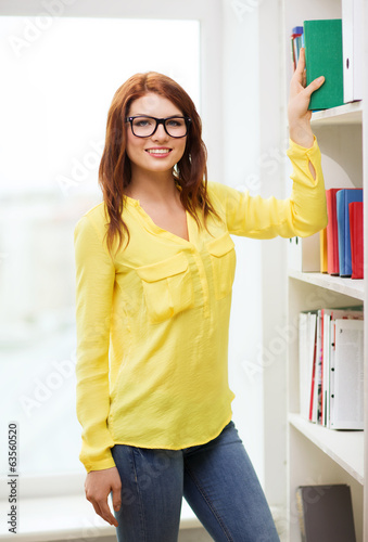 smiling female student in eyeglasses choosing book
