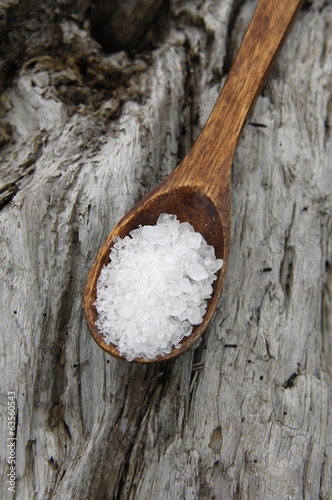 Spa salt in wooden spoon on rustic wood texture