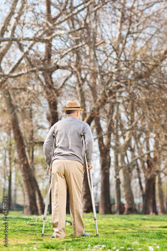 Elderly gentleman with crutches, walking in park