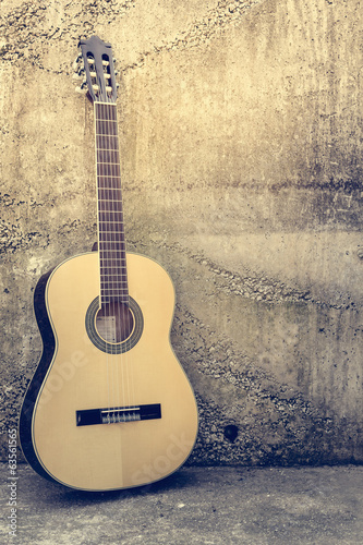 Acoustic guitar against a grunge textured wall.