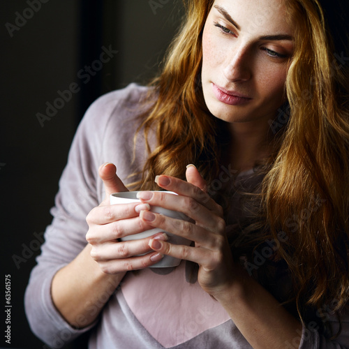 Beautiful and relaxed girl sitting and drinking tea