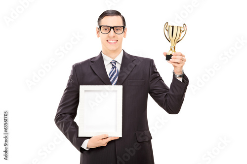 Man holding a trophy and a picture frame