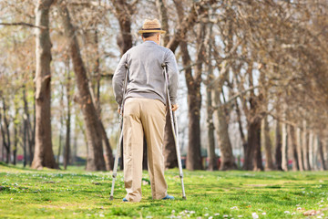 Old man with crutches, walking in the park