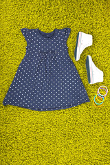 Beautiful dress and gumshoes for little girl on green carpet
