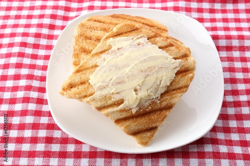 Grilled bread with butter on tablecloth