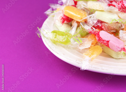 Tasty candies on plate on purple background