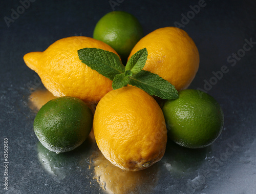 Lemons and limes on dark background