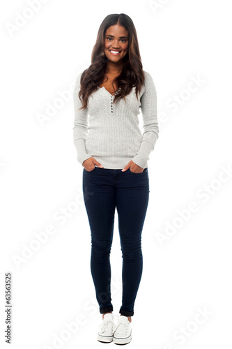 Smiling young woman posing with hands in pockets