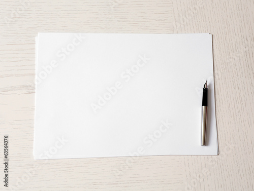 Blank paper and pen on wooden table