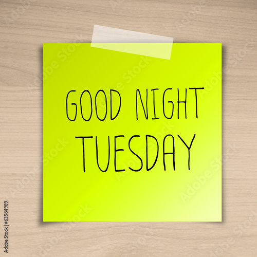 Good night tuesday sticky paper on brown wood background texture