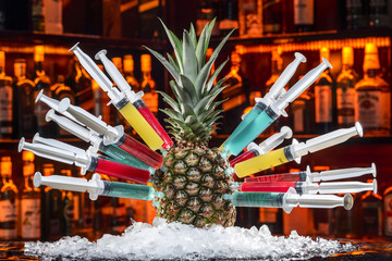 colorful cocktails with pineapple in the syringe handle