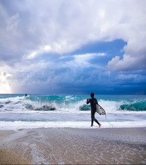 Young male surfer standing looking out at ocean.