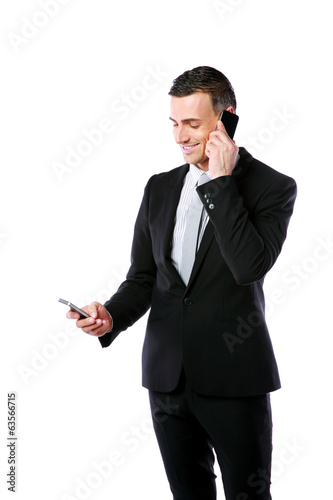 Happy busy businessman using two mobile phone