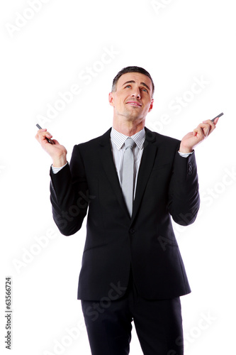 busy caucasian businessman holding two cell phones