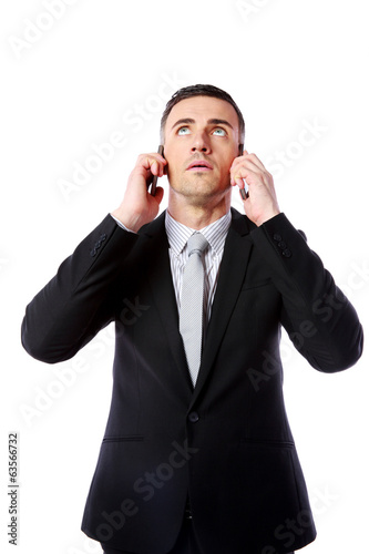 Businessman talking on two cell phones at the same time