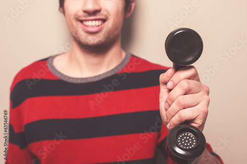 Happy young man holding telephone