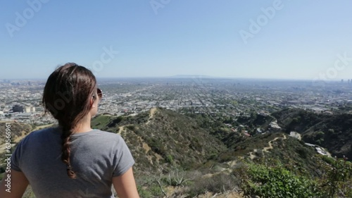 Woman looking at view of a city from the top of a mountain