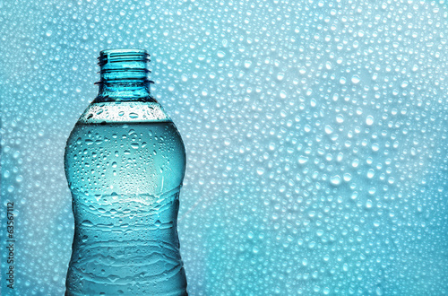 aqua bottle on background with drops