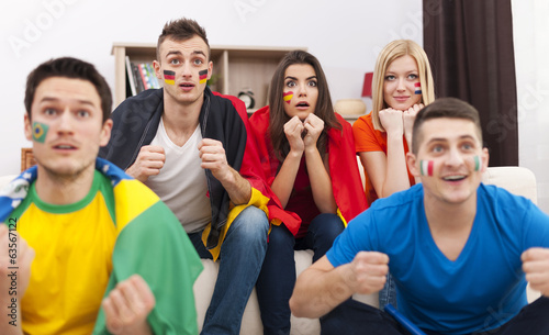Portrait of young soccer fans during the watching match on TV