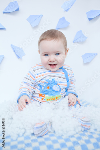 Smiling cute baby in nursery playing with white down