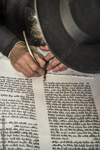 an orthodox jew hand writing a torah script