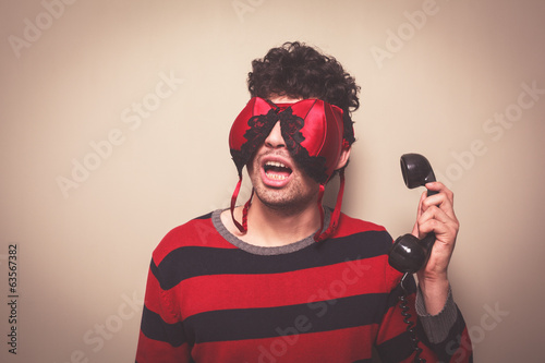 Man with bra on face holding telephone