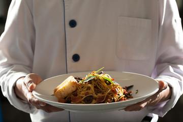 spaghetti, chef in uniform holding a dish of seafood spaghetti