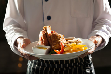 german pork,chef in uniform holding a dish of german pork leg