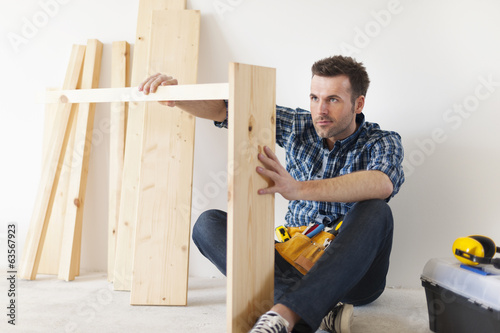 Handsome carpenter working on new furniture