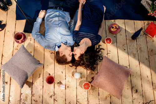 couple lying on wood floor with pillows and sweets