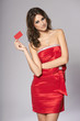 Fashion female in red cocktail dress showing red card