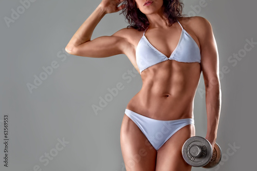 muscular athletic young woman in a white bathing suit on a gray
