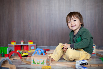 Little toddler boy playing with wooden railway, indoors.