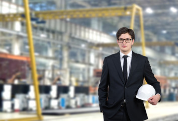 Engineer in holding a white cap, factory background.