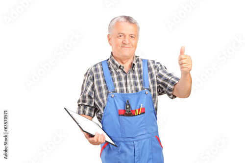 Male mechanic holding clipboard and giving thumb up