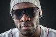 Confident black man close up portrait with sunglasses against da