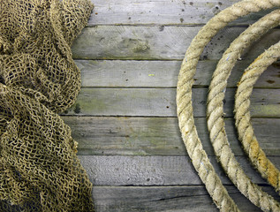 Wooden background with net and rope roll