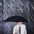 Businessman with black umbrella protecting from rain