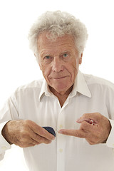 Elderly  diabetic man measuring sugar level in blood