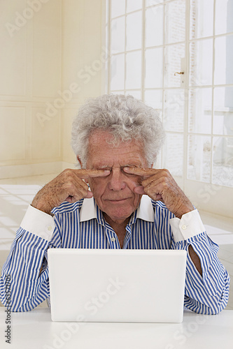 Senior businessman in front of laptop rub eyes