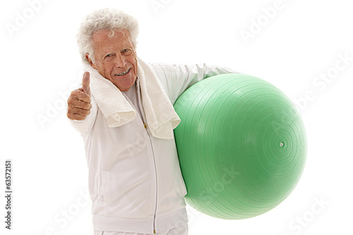 Happy elderly man thumb up with a fitball on white background