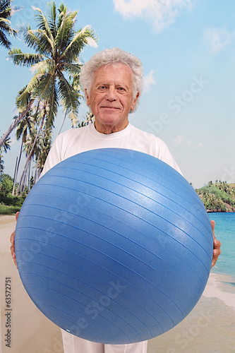 Elderly man doing yoga exercises with a gym  ball