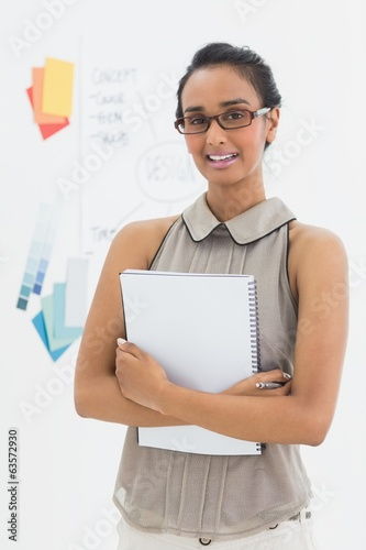 Designer holding notepad and smiling at camera