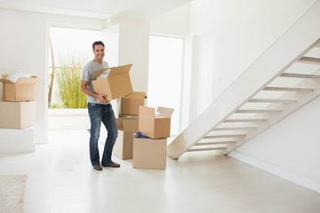 Smiling man carrying boxes in a new house