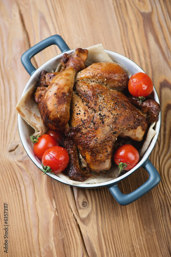 Baked chicken with tomatoes, wooden background, above view