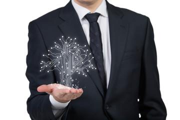 Businessman holding microchip tree
