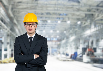 Businessman in a yellow cap, warehouse background