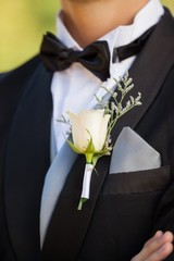 Mid section of flowers on lapel of male
