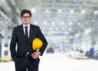 Businessman holding a yellow cap, warehouse background