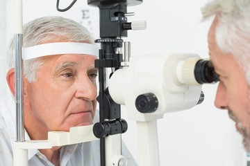 Optometrist doing sight testing for senior patient